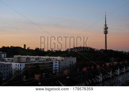 Olympic tower rises behind buildings in MunichGermany late in the afternoon