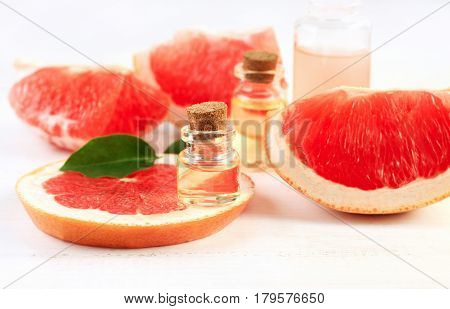 Little glass vial of aroma essential oil on grapefruit fresh slice, citrus pieces background.