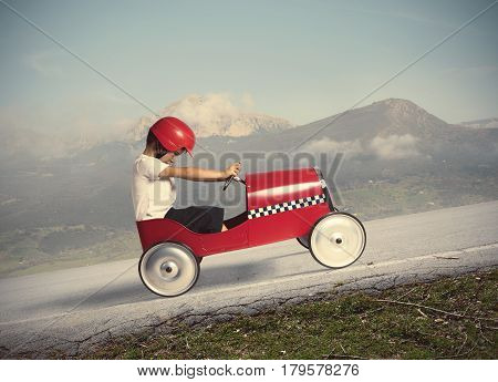 Child climb a mountain with a small toy car
