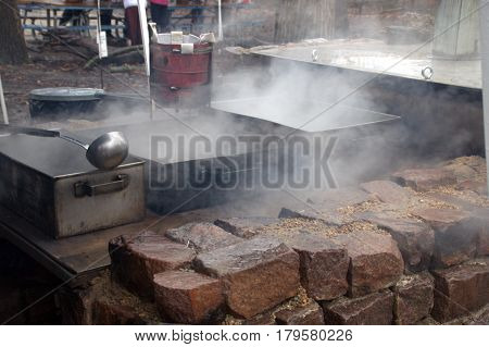 making maple syrup by boiling the sap in metal pots and pans, on an outdoor wood burning brick kiln