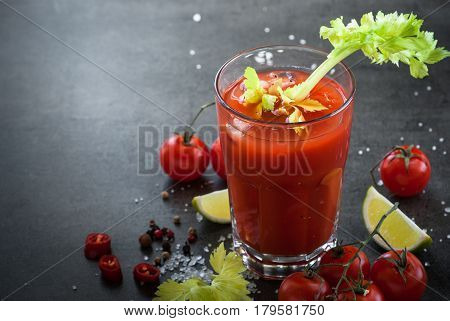 Bloody Mary cocktail. Alcoholic drink and ingredients at dark slate table.