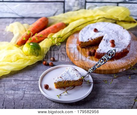 Piece of pumpkin-carrot cake. Pie on the plate. Near filbert. Vegetables and pie on the background. Сoncept of home-eating