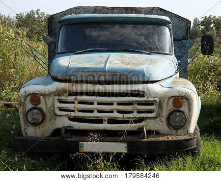 Old truck with a blue and white painted cabin abandoned in the grass