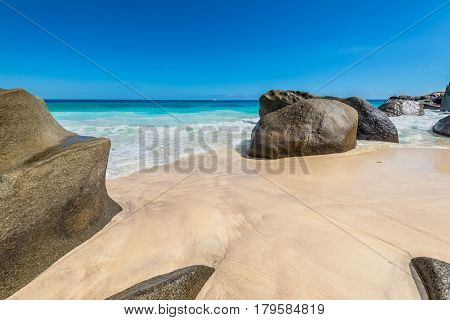 Seascape with large granite boulders and blue summer sky. Sunny day on Carana beach of Seychelles.