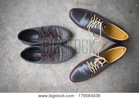 Two different Pairs of brown classic modern shoes on the floor background Conceptual shooting of shoes