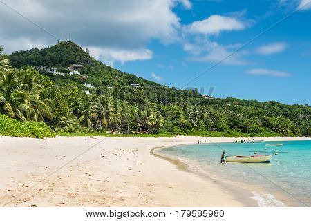 Anse Royale Mahe Island Seychelles - December 15 2015: Spectacular Anse Royale beach and in the background some people enjoying the tropical beach Mahe Island Seychelles.