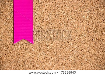 Pink ribbon on cork board texture background