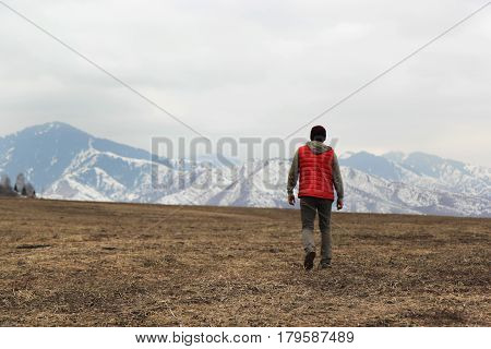 lonely man in red waistcoat walking toward mountains background.