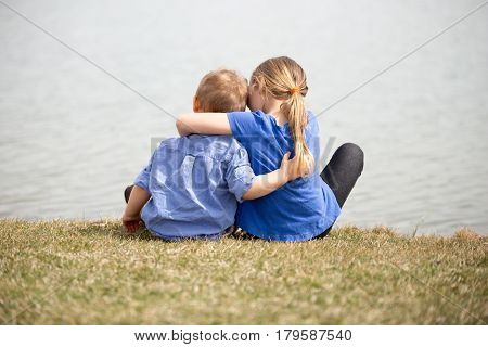 Young sibling boy and girl looking at the lake holding eachother.