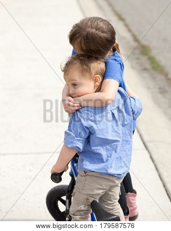 Young boy and girl sibling hugging with toddler boy on bike and sister hugging.