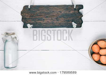 White wood background of milk and egg shop or store department. Bottle of milk and chiken eggs in sieve. Rustic style. Wooden signboard as a title. Top view