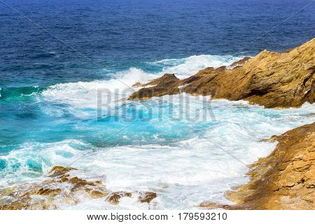 Waves break on rocky shore. Raging sea an elemental power in a storm. Clear day at sea coast. Tourist beach resort in village Bali Crete island Greece Beach Evita