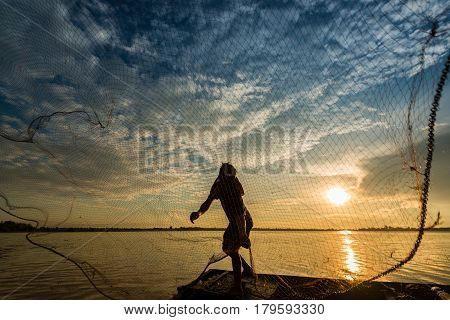 Fisherman is fishing by using fishing net on the river during in the evening during sunset