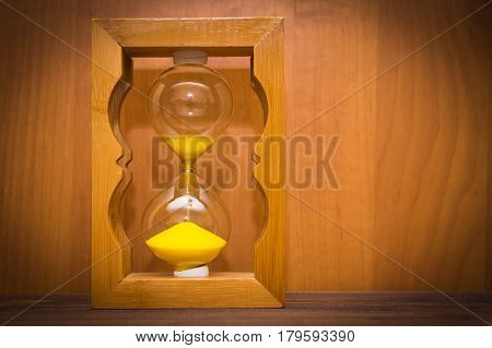 Hourglass on wooden background. Concept of passing time for business deadline, urgency and running out of time.