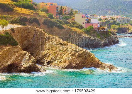 Classic resort Greek architecture buildings stands on shore of Cretan sea. Waves break on rocky shore. Clear day at sea coast. Tourist beach resort in village Bali Crete island Greece Beach Evita