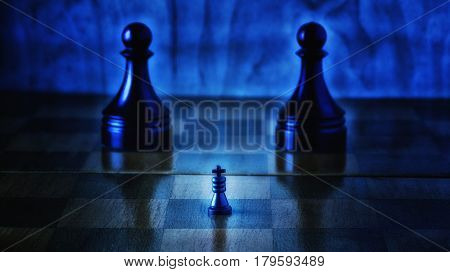 A small black chess king and big pawn servants chess is an exciting and popular game all over the world actions take place on such a wooden board