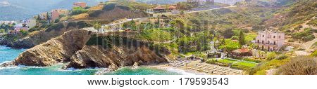 Sandy Evita and Karavostasi beach in sea bay of resort village Bali. Views of shore washed by waves and sun loungers with parasols where sunbathing tourists. Hotel and tavern buildings. Crete Greece