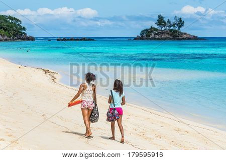 Anse Royale Mahe Island Seychelles - December 152015: Girls walking in the sand in Spectacular Anse Royale beach and in the background some people enjoying the Anse Royale Beach Mahe Island Seychelles.