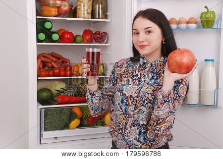 Beautiful smiling young girl holds a glass of pomegranate juice and garnet on the fridge background