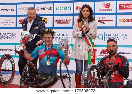 Rome Italy - April 2 2017: Alex Zanardi is the winner of the hand bike race of 23 ^ Rome Marathon. On stage together with the mayor Virginia Raggi during the award ceremony.