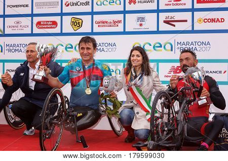 Rome Italy - April 2nd 2017: Alex Zanardi is the winner of the hand bike race of 23 ^ Rome Marathon. On stage together with the mayor Virginia Raggi during the award ceremony.