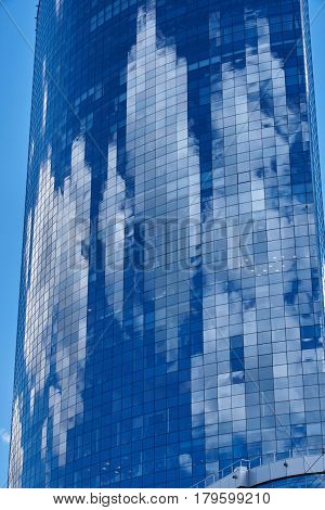 Cumulus clouds are reflected in the glass wall of a multistory building. Background