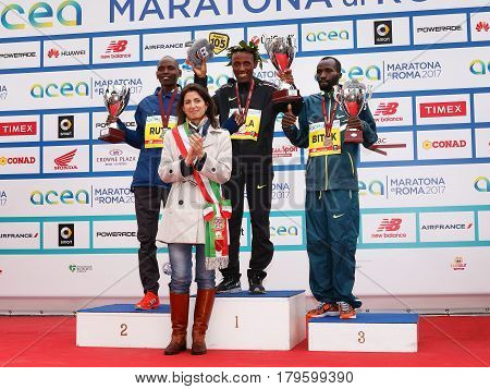 Rome Italy - April 2 2017: The mayor of Rome Virginia Raggi on stage with the top three finishers in the men's race of the 23rd marathon in Rome. At the center of Tola Shura Kitata first place. To his right Dominic Ruto Kipngetich second place. To his lef