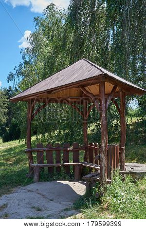 Wooden arbor on the background of trees in the park