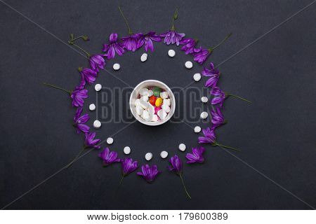 violet spring flowers and tasty marshmallow zephyr with dragee and sprinkles sweets in cup on grey background copy space on grey background copy space