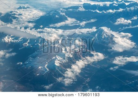Idyllic Snowy Mountain Peaks Under Clouds From Plane