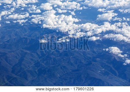 Idyllic Bald Mountain Peaks Under Clouds From Plane