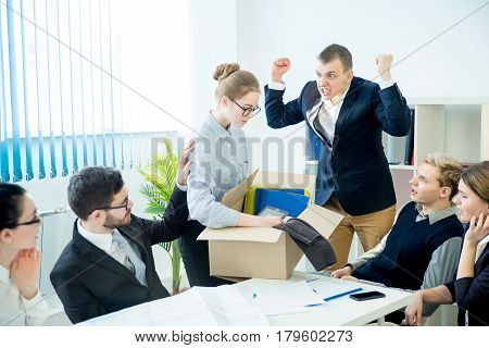 An angry boss is shouting on his employee