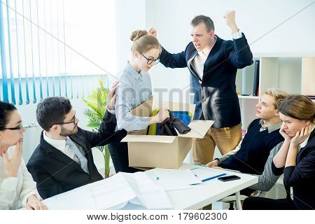 An angry boss is firing his employee