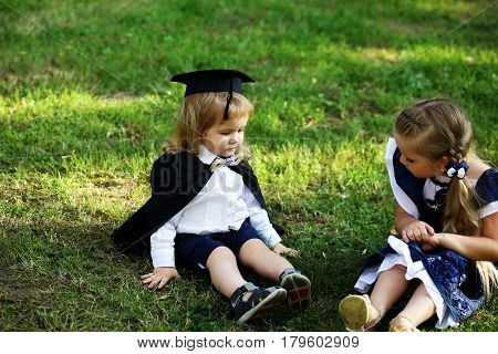 Cute Little Children Sitting On Green Grass