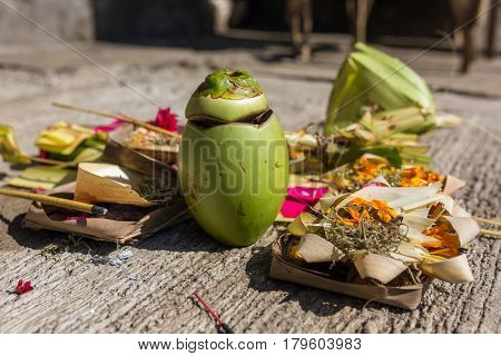 Traditional offerings to gods in Bali with flowers, food and aroma sticks