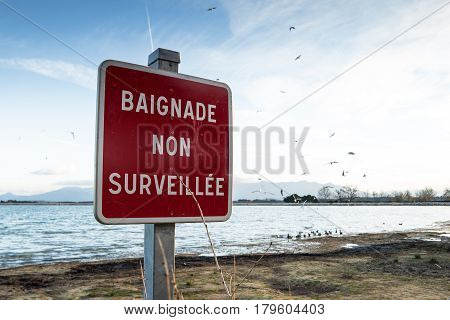 Closeup of a French warning sign of a non supervised swimming lake