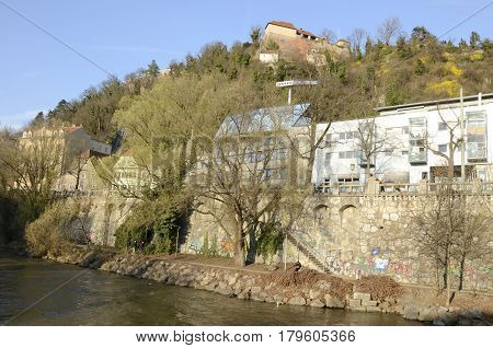 GRAZ, AUSTRIA - MARCH 20, 2017: Buildings at the riverbanks of the river Mur and the hill of Schlossberg in Graz the capital of federal state of Styria Austria.