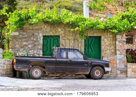 Bali Greece - April 30 2016: Old black pickup truck Mitsubishi L200 parked under a mountain in background of stone wall of the barn. Easy 4wd truck Japanese production. Resort village Bali Crete
