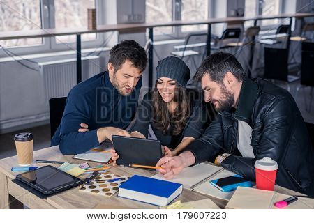 Video conference of young smart team. Group of modern people discussing project on video conference on tablet in the office. Working environment with tablets coffee notepads and stationery.