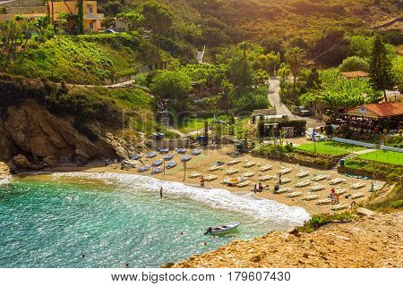 Bali Greece - April 30 2016: Sandy Evita and Karavostasi beach in sea bay of resort village Bali. Views of shore washed by waves and sun loungers with parasols where sunbathing tourists