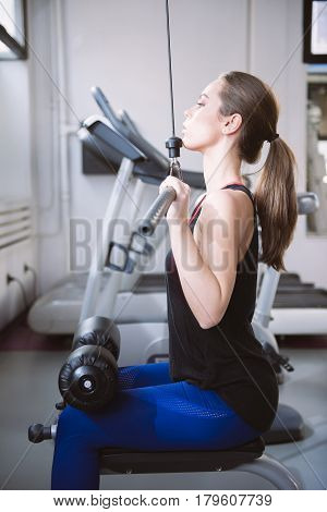 Attractive Young Woman Working Out On Weight Lifting Training Machine