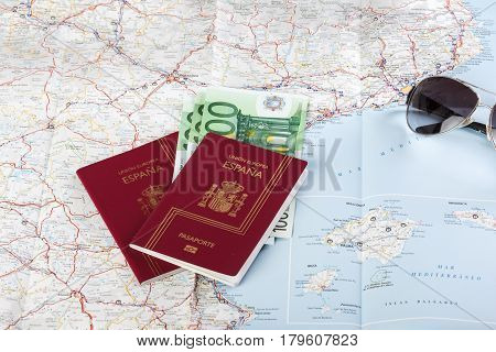Spanish passports with european union currency and glasses on a map background. Travel concept.