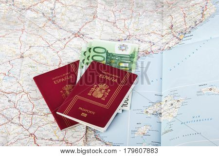 Spanish passports with european union currency on a map background. Travel concept.
