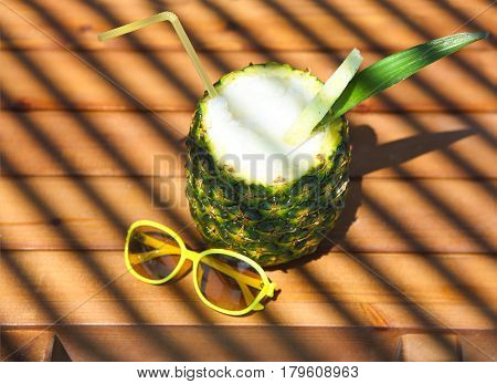 Pineaple exotic cocktail on wooden background Pina colada with yellow sun glasses