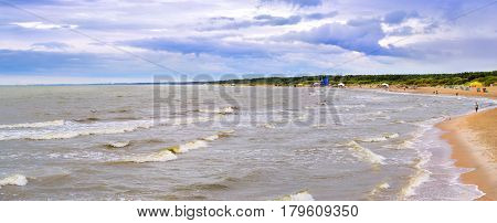 Strong waves on a stormy overcast day washed by the Baltic sea coast. Few tourists walk along a sandy beach in the resort town of Palanga Lithuania Klaipeda