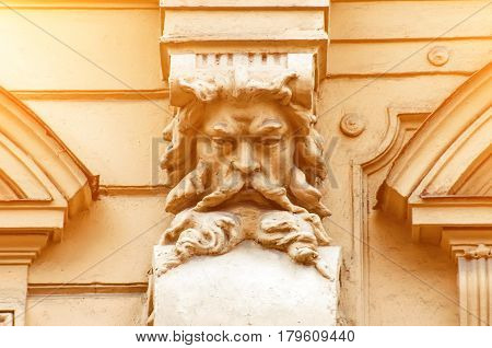 An Old Stucco Face Of A Man With A Beard On The Building
