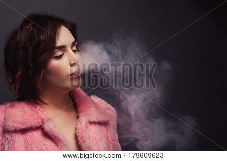 Young beautiful female in pink fur coat breathing out pink smoke on dark background.