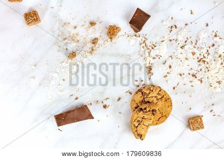 The process of making chocolate chips cookies. Overhead shot of biscuits with grated chocolate, cane sugar, flour, and copy space