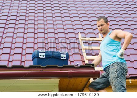 Repairman looks at the box with a tool on the roof