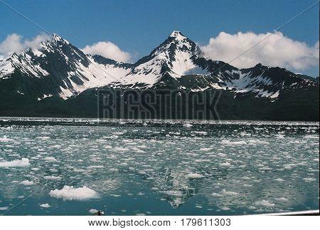 Ice Chunks Floating In Ocean Near Mountains Of Seward Alaska